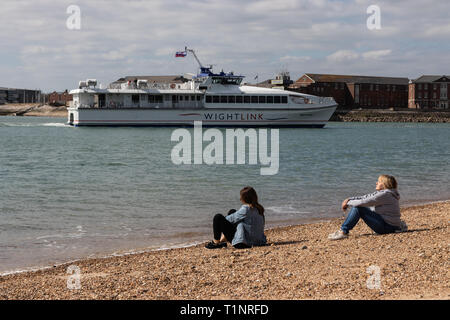 Mother and daughter enjoying the sun on the beach at Old Portsmouth pebble beach - Stock Photo