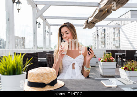The girl in the cafe. Sniffs and enjoys coffee, inhales the aroma gets pleasure from the smell of tea. Relaxing summer restaurant on the veranda - Stock Photo