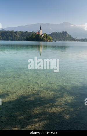 The sun rises above Lake Bled on a clear day. The mountains are visible behind the church on the island at Lake Bled. - Stock Photo