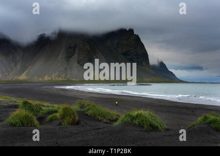 Colorful panorama of the Stokksnes headland on southeastern Icelandic coast with Vestrahorn (Batman Mountain). Iceland, Europe. Lonely man walking alo - Stock Photo
