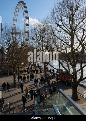 Tourists and Londoners walk along the river Thames on the South Bank near the London Eye and enjoy the warm sunshine on an afternoon in late March. - Stock Photo
