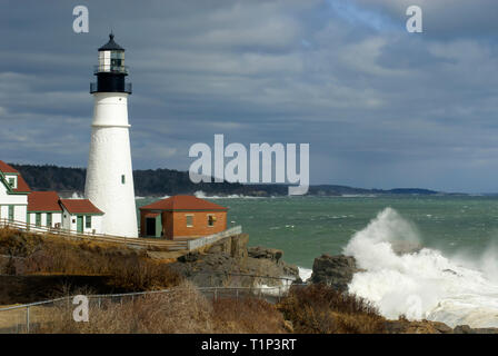 Sunlight illuminates Portland Head lighthouse, through storm clouds, as giant wave breaks over rocks, in Maine. - Stock Photo