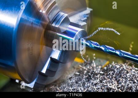 Drilling detail. Lathe working. Turning. Twisted metal swarf pile. Clamped metallic workpiece Rotating machine tool. Blue steel drill bit. Manufacture. - Stock Photo