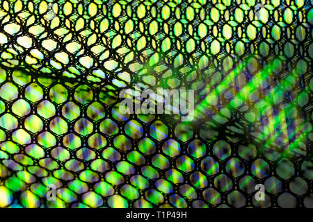Wavy netting. Light rays artistic detail. Abstract mesh texture. Green lightbeams glowing through black hexagonal cells. Shiny grid pattern background. - Stock Photo