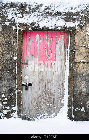 Old pink wooden stone shed door in Leadhills village in the early morning snow. Scotlands second highest village. South Lanarkshire, Scotland - Stock Photo