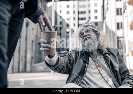 Distressed long-haired man being poor homeless and collecting money - Stock Photo