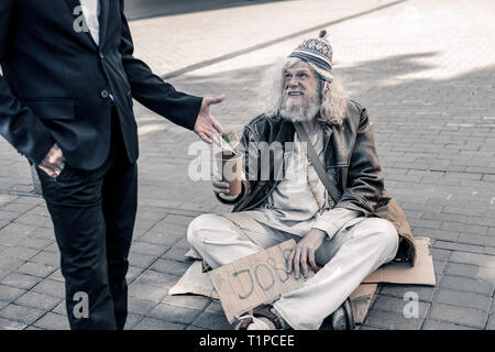 Filthy grey-haired poor man being jobless and living on street - Stock Photo