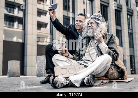 Excited grey-haired old man being extremely happy with money - Stock Photo