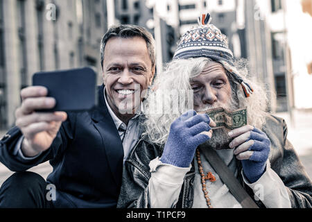 Wild grey-haired dirty man being focused on money in his hands - Stock Photo