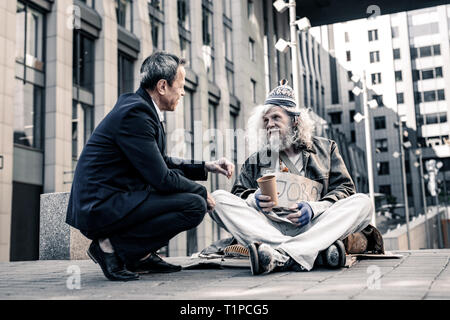 Short-haired man in dark costume being extremely kind to senior homeless - Stock Photo