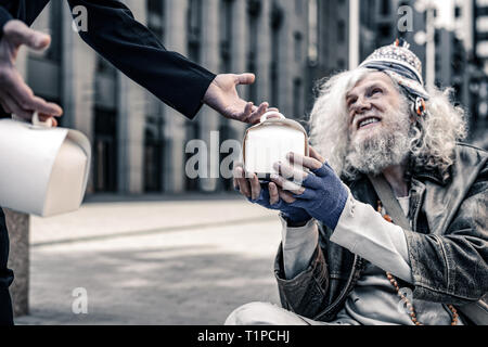 Cheerful long-haired poor man being excited while receiving box with food - Stock Photo