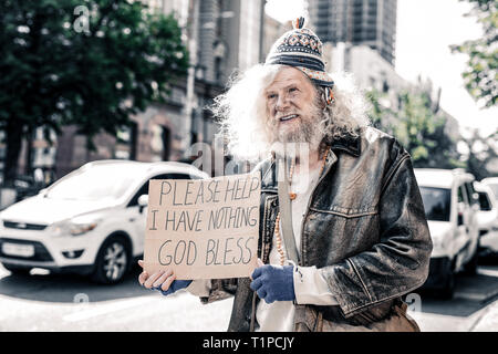 Miserable dirty old man being poor homeless and standing with cardboard - Stock Photo