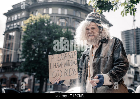 Confused senior homeless man being dirty and washed - Stock Photo