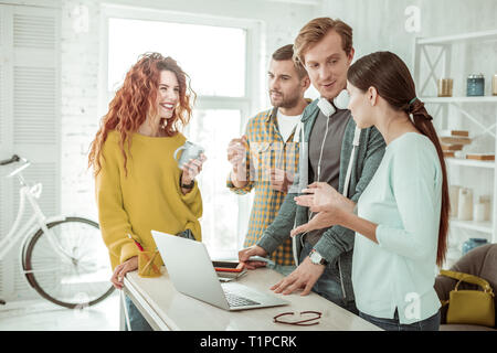 Good looking young people speaking about work - Stock Photo