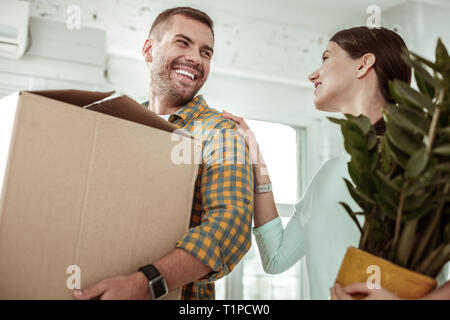 Positive young woman putting her hand on colleagues shoulder - Stock Photo