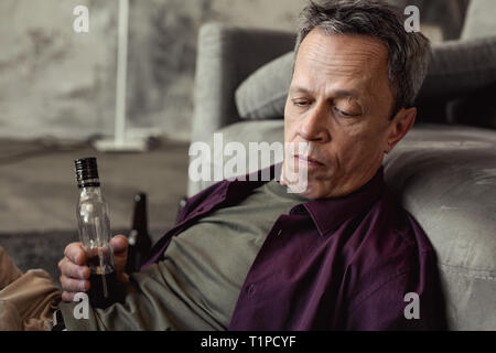 Unhappy old man being in bad state while drinking a lot of alcohol - Stock Photo