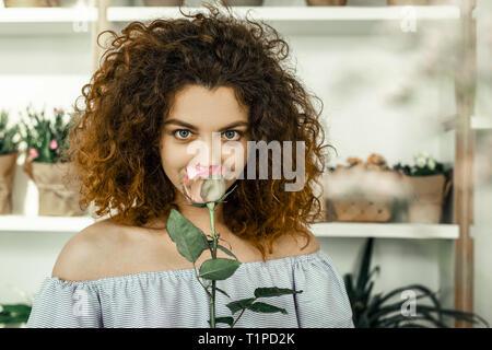 Beautiful blue-eyed florist feeling inspired smelling nice pink flower - Stock Photo