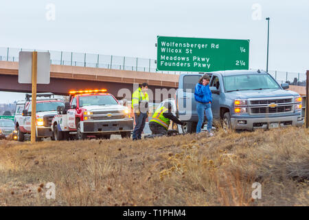 Woman motorist receiving assistance for flat tire along Interstate 25 in evening, Castle Rock Colorado US. Photo taken in March. - Stock Photo
