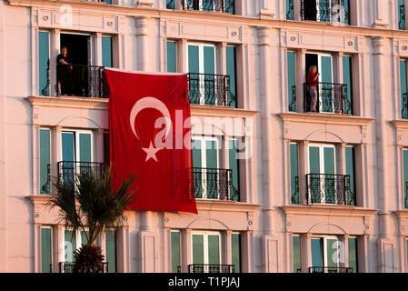 Izmir, Turkey - October 29, 2018: Turkish flag hanging on a building with two person at Alsancak Izmir Turkey. - Stock Photo