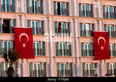 Izmir, Turkey - October 29, 2018: Turkish flags hanging on a building with two person at Alsancak Izmir Turkey. - Stock Photo
