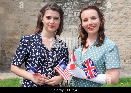 2 young ladies celebrating victory holding flags of the liberating nations France, USA, Canada and the UK in Sainte-Mere-Eglise (Normandy), France - Stock Photo