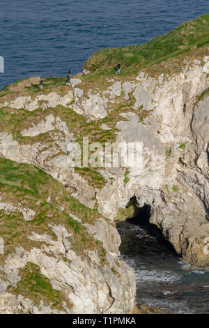 Young people walking along a narrow clifftop path over a sea arch in limestone rock at Kinbane Head, County Antrim, Northern Ireland. - Stock Photo
