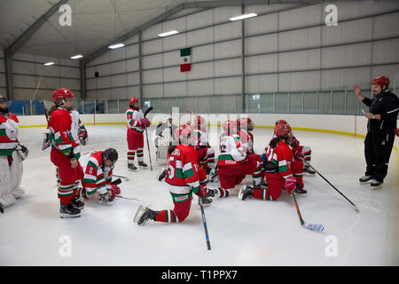 """Diego de la Garma (R), 38, the head coach of the Selección femenil de México de hockey sobre hielo, explains a drill to his team during a training session over the course of a 3-day intensive training week-end at the Winter Sports Center Metepec in Metepec, State of Mexico, Mexico on March 9, 2019. Diego is the head coach of both the men and women's national ice hockey teams in Mexico. He is the son of the founder of the Mexico Ice Hockey Federation and started to play ice hockey at age 12. """"This is our way of leaving a mark on Mexican society, to generate a deep change in this country,"""" he sa - Stock Photo"""