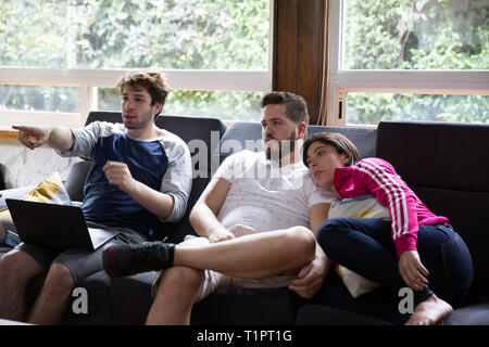 Macarena Cruz Ceballos, 23, one of the defenders of the Selección femenil de México de hockey sobre hielo, watches an ice hockey match on television with her family and boyfriend at their home in Mexico City, Mexico on March 17, 2019. Macarena lives with her parents in San Jerónimo Lídice, an affluent residential neighborhood in Mexico City. Her brother lives in Canada, where he plays ice hockey in the Junior League. She studies economics and finance at the Monterrey Institute of Technology, at the Mexico City campus. She started figure skating at age 5 and ice hockey at age 12. She is one of  - Stock Photo