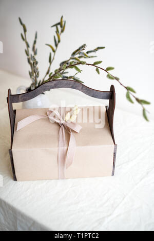 Gift box with spring flowers on light natural fabric background. Easter basket with presents - Stock Photo