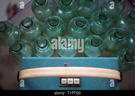 empty bottles next to antique radio - Stock Photo