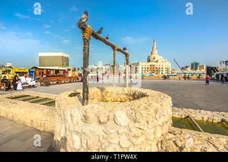 Doha, Qatar - February 20, 2019: pigeons at old well fountain, famous landmark at Souq Waqif. Middle East, Arabian Peninsula. Fanar Islamic Cultural - Stock Photo