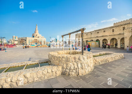 Doha, Qatar - February 20, 2019: old well fountain, famous landmark at Souq Waqif and Fanar Islamic Cultural Center with Spiral Mosque and Minaret on - Stock Photo