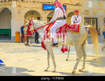 Doha, Qatar - February 20, 2019: closeup of Police on horse in traditional clothes at Souq Waqif riding white Arabian Horses. Popular tourist - Stock Photo