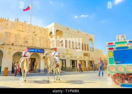 Doha, Qatar - February 20, 2019: Police on horse at Souq Waqif riding white Arabian Horses. Popular tourist attraction in Middle East, Arabian - Stock Photo