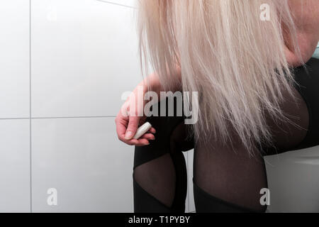 woman sitting on toilet with tampon in her hand to illustrate menstruation. - Stock Photo