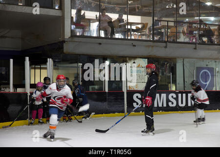 Frida Cárdenas Castro (C), 21, one of the forwards of the Selección femenil de México de hockey sobre hielo, during a training session with the junior ice hockey players at the San Jerónimo ice rink in Mexico City, Mexico on February 26, 2019. Frida lives with her family in Doctores, a working class neighborhood in Mexico City. She is in her second year of marketing at the Mexico Anáhuac University, where she has a high performance athlete scholarship. She started roller in-line hockey at age 6 and transitioned to ice hockey at age 14. Her family is also athletic and supportive of her hockey-r - Stock Photo