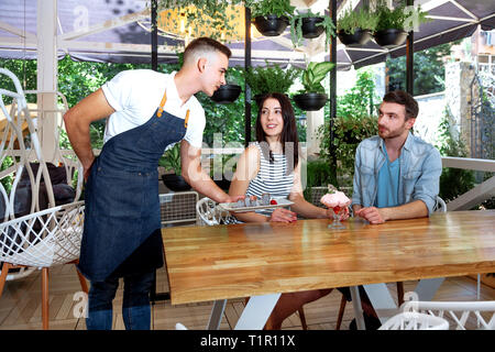 A friendly waiter gives desserts and ice-cream to visitors in a cafe. Young and beautiful guy with a girl in a white cafe with green leaves on the rom - Stock Photo