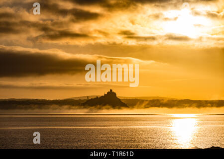 Penzance, Cornwall, UK. 28th Mar, 2019. UK Weather. The sun rises above St Michaels Mount, with mist rolling in from the land this morning. Credit: Simon Maycock/Alamy Live News - Stock Photo