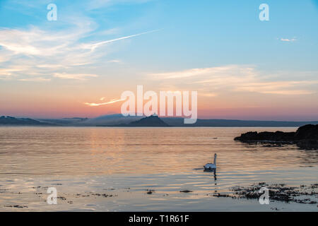 Penzance, Cornwall, UK. 28th Mar, 2019. UK Weather. A pair of swans were out on the sea at Penzance at sunrise this morning, with a misty St Michaels Mount in the background. Credit: Simon Maycock/Alamy Live News - Stock Photo