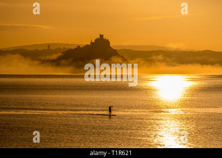Penzance, Cornwall, UK. 28th Mar, 2019. UK Weather. Paddleboarders were out at 5am this morning to make it across the sea at Mounts bay the for the sunrise over St Michaels Mount. Credit: Simon Maycock/Alamy Live News - Stock Photo