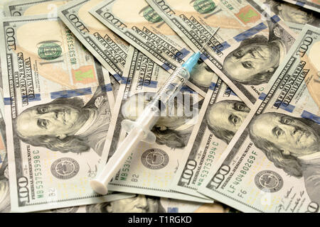 close up of syringe with injection on dollar banknotes - Stock Photo