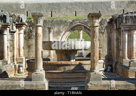 Detail of the outdoor ruins of the Santa. Clara monastery premises in Coimbra (Portugal) showing a stone fountain surrounded by ornate columns. - Stock Photo