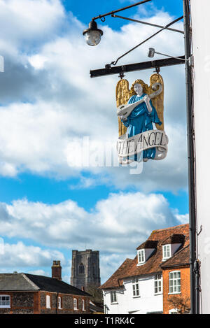 The Angel pub sign in front of the Market Square with St Peter and St Paul's Parish church to the rear. Lavenham village, Suffolk, England, UK. - Stock Photo