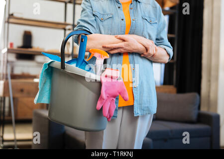 Hard-working mature woman in jeans jacket holding bucket - Stock Photo