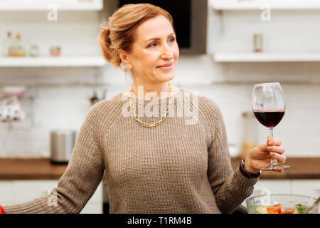 Beaming good-looking mature woman in beige sweater - Stock Photo