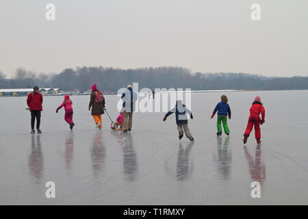 Kids, teenagers and grown-up enjoying ice skating on the Amsterdam lake the Nieuwe meer in the Netherlands. - Stock Photo