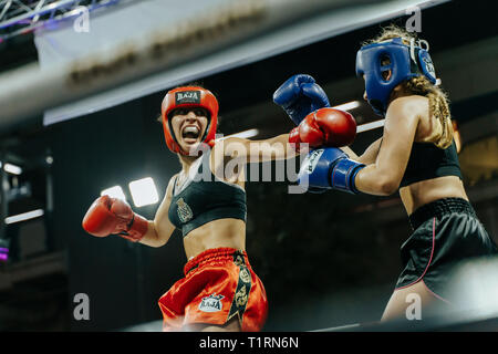 two female muay-thai fighters during a competition in Bangkok, Thailand - Stock Photo