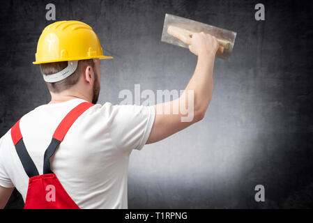 Rear view of a worker plastering a wall indoors - Stock Photo
