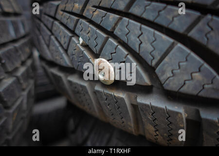 Closeup of a used and useless car tyre pierced with a metal rivet - Stock Photo