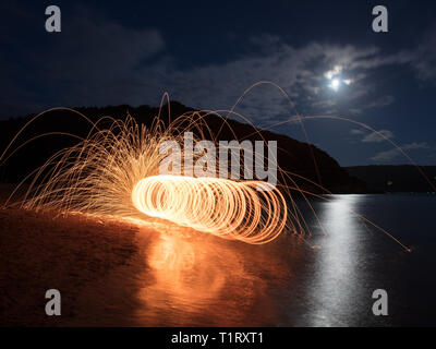 A steel wool shot on East Portlemouth beach in Devon. Steel wool photography involves using a whisk,steel wool and a dog lead. - Stock Photo